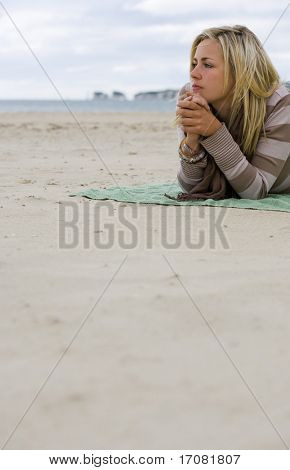 A beautiful blond haired blue eyed young woman laying alone on a beach deep in thought