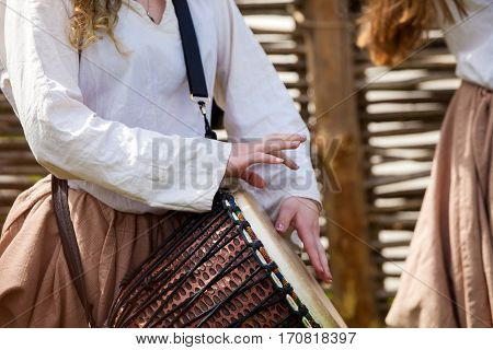 Girl playing african djembe drum on the street