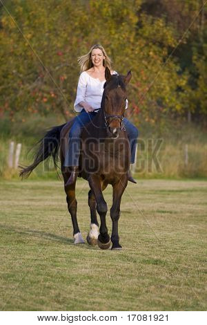 An attractive young woman riding a horse bareback during the fall with an apple orchard in the background