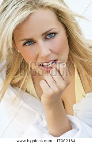 A beautiful blond haired blue eyed model wearing a white shirt looking sexy and thoughtful, shot outside in natural golden light