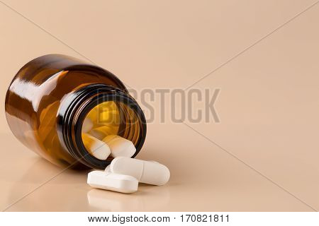 Pills bottle and heap of white pill on beige background