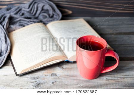Selective Focus Photo Of Grey Cozy Knitted Scarf With Cup Of Coffee Or Tea And Open Book On A Wooden