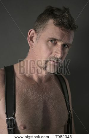 portrait of handsome shirtless man with leather suspenders