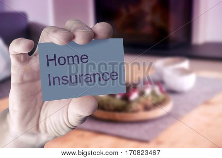 closeup of mans hand showing business card with the words Home Insurance in front of living room