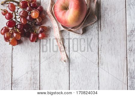 Top view of Red grapes with apple and measure tape on white wooden table background Free space for text