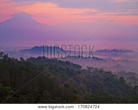 The sun rises on a foggy morning over Borobudur temple near Yogyakarta Indonesia.