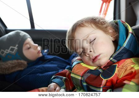 Two brothers sleeping in a child car seat