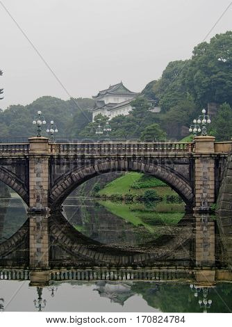 A traditional stone bridge reflects in the still water in front of the Japanese Imperial Palace in downtown Tokyo.