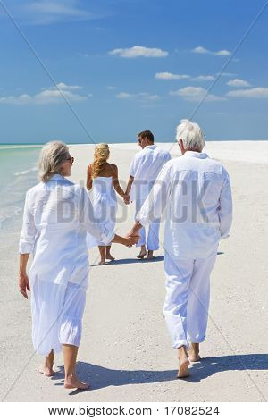 Two couples, generations of a family together holding hands and walking on a tropical beach
