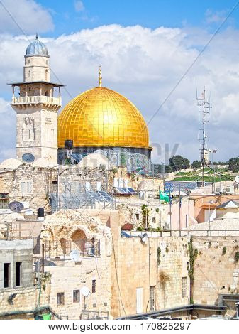 The golden dome of the mosque on the Temple Mount dominates this city view of historic Jerusalem Israel.