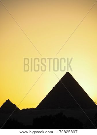 A silhouette of the great pyramids of Egypt in Giza outside of Cairo.