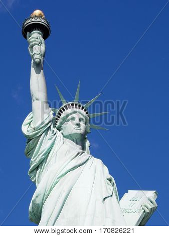 The Statue of Liberty on a sunny day in the harbor of New York City.