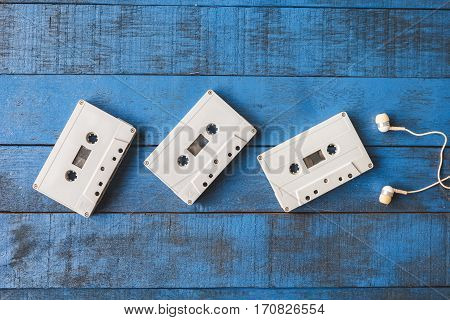 Top view of Audio tape with earphones on blue wooden table background