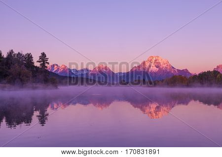 a scenic sunrise reflection in the Tetons in fall