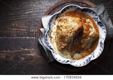Juicy Butter chicken in a bowl with wavy edges on the boards horizontal