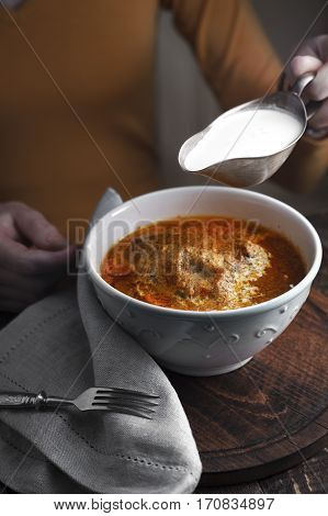 Butter chicken sauce-boat with cream and a woman at the table vertical