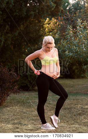 Fitness pregnant woman feeling her baby push. Happy gravid blonde touching her belly while doing fitness exercises at nature. Pregnancy sport at nature, healthy lifestyle, body care concept