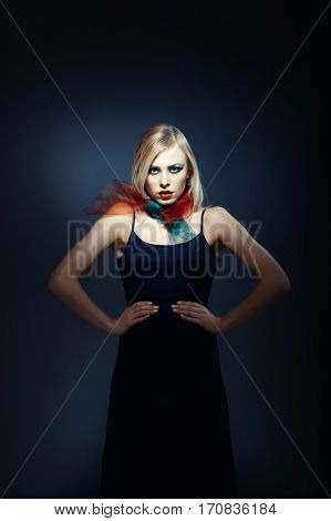 Elegant blond lady in stylish clothes on a dark background