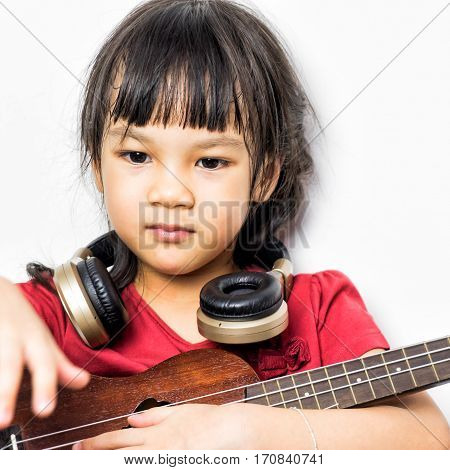 guitar kids girl asian kid young background white little fun child music portrait playing female person happy beautiful cute guitarist play isolated teen instrument musician musical beauty acoustic happiness sitting headphone