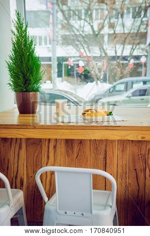Cafe Table At The Window With View Of Active City And Served With A Breakfast Of Fresh Pastries And