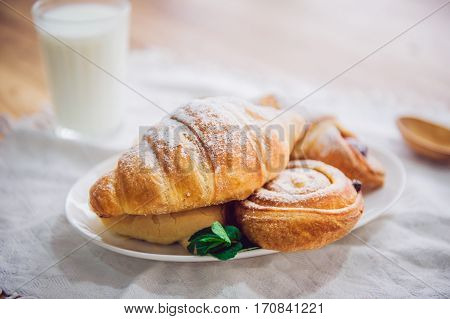 Close Up Continental Breakfast With Assortment Of Fresh Pastries And Glass Of Milk On The Background