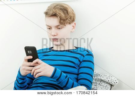 Serious Young Teenage Boy Reading A Message