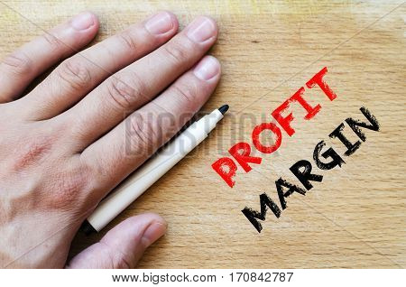 Human hand over wooden background and profit margin text concept