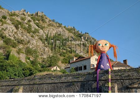 KOTOR OLD TOWN, MONTENEGRO - JULY 19, 2016: giant Pippi Longstocking on the wall of Kotor Old Town is installation art of Kotor Festival of Theatre for Children; on background St. John fortification