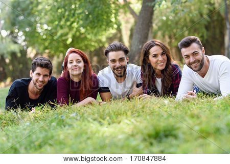 Group of young people together outdoors in urban park. Women and men laying on grass wearing casual clothes.