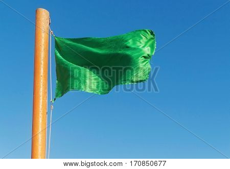 Develop Green Flag On A Background Of Blue Sky