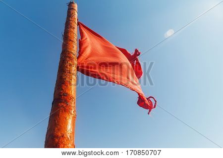Red Flag To Develop On The Background Of Blue Sky