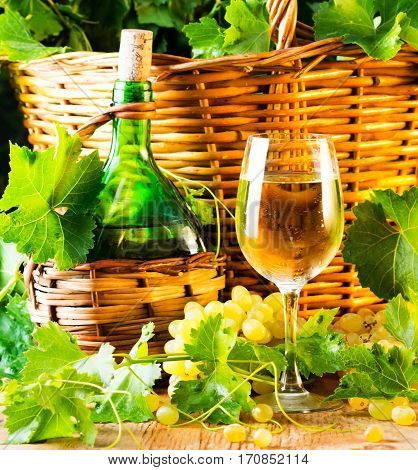 Glass and bottle of white wine basketof grapes. wooden background