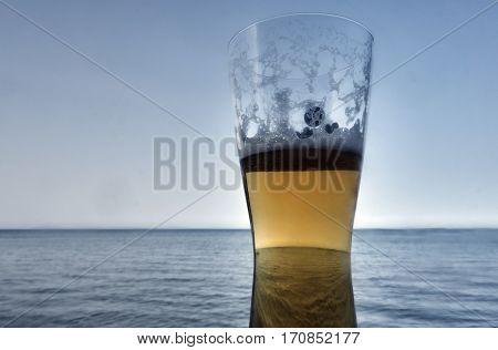 Trophy with a beer on the background of the sea in a Greek taverna