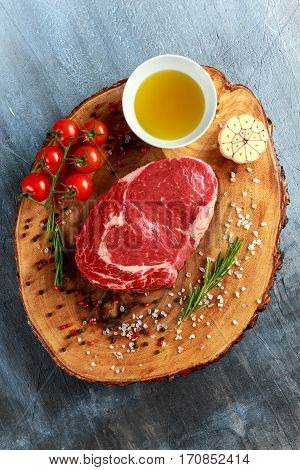 Fresh Raw Beef Steak Ribeye, with salt, peppercorns, rosemary, tomatoes and olive oil.