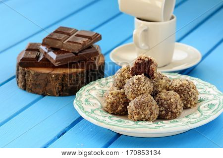 Homemade tasty chocolate truffles chocolate bars and coffee cups on bright blue background closeup