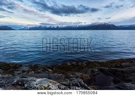 Sunset over snow caped mountain range by Norwegian fjord