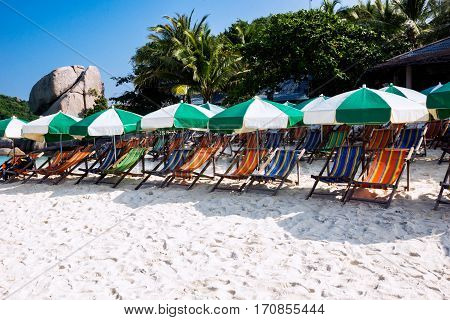 Recliners under parasols on beautiful tropical beach in Thailand