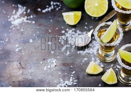 Alcohol, junk food, party, holidays concept. Golden mexican tequila shot on a grunge black table with salt and lime. Copy space background