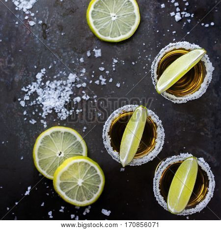 Alcohol, junk food, party, holidays concept. Golden mexican tequila shot on a grunge black table with salt and lime. Top view flat lay overhead