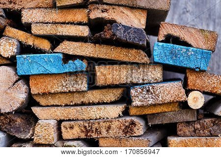 Stack of sawn boards with slices of different shapes. Two planks painted in blue color and stand out among the other