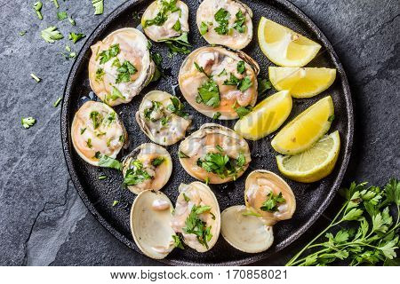 Fresh raw clams with lemon, herbs and white wine on black iron plate on stone slate background. Top view.
