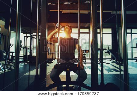 Handsome man resting during a workout and drink water at the gym