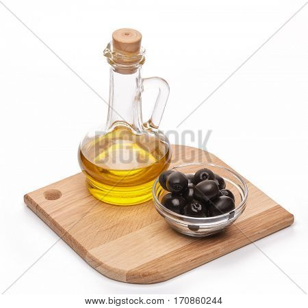 Glass cruet with Extra virgin olive oil, canned black olives in bowl stand on a wooden cutting board on a white background.