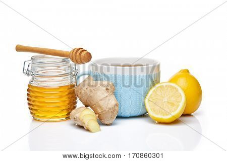 Honey in glass pot  and blue cup of tea with ginger and lemon on a white background.