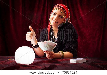 Studio shot of gypsy fortune teller makes quite good money giving you advice over the phone