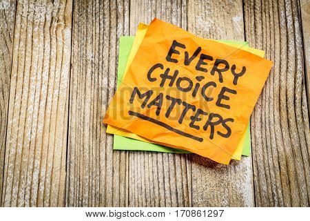 every choice matters - reminder on a sticky note against grunge wood board
