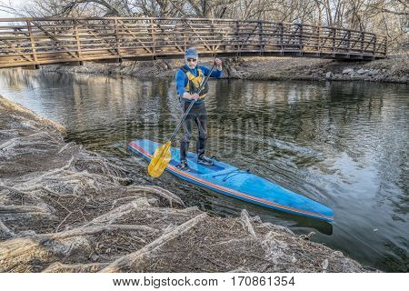 Stand up paddling on the Poudre RIver - a summer day like day in the middle of winter in northern Colorado