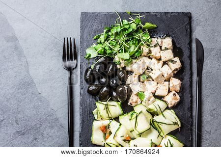 Salad with zucchini, cheese feta, olives and rucola on black slate plate on gray slate background. top view