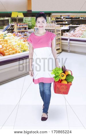 Portrait of young woman shopping in grocery while holding shopping cart