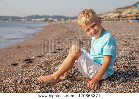 Happy smiling small boy sitting on the beach and playing with stones. Hands in motion blur. Selective focus.